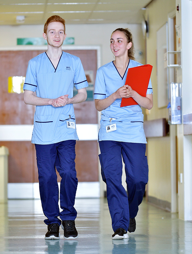 Male and female in hospital uniforms walking through corridor