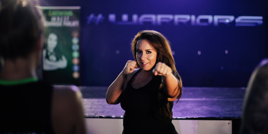 Dominique in a punching pose dressed in all black with her logo in the background that spells Warrior