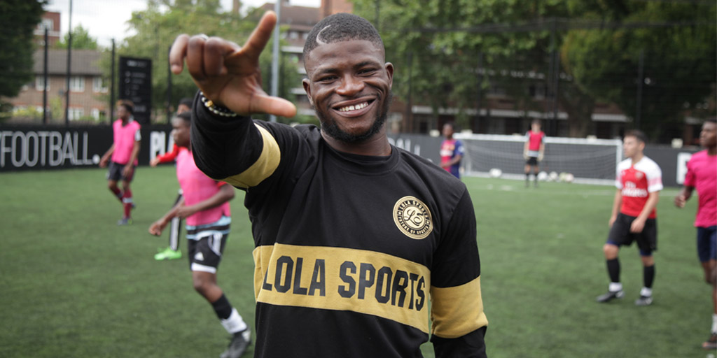 Abiola in a black and gold jersey that says Lola Sports, gesturing a number with his hand in a football filed with boys playing football in the background.