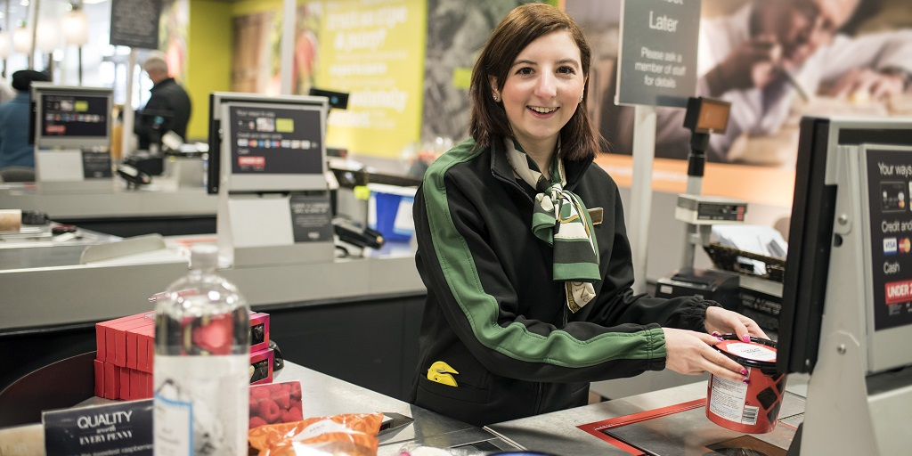 Young girl at supermarket checkout