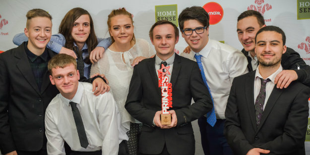 A group of young people standing for a group photo holding up a Prince's Trust Award