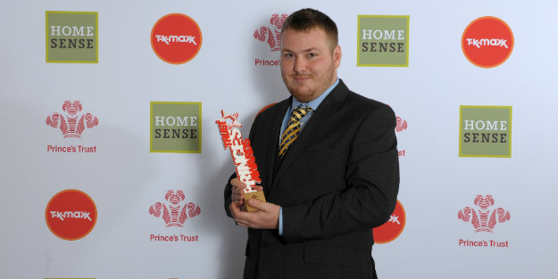 A young person holding a Prince's Trust Award