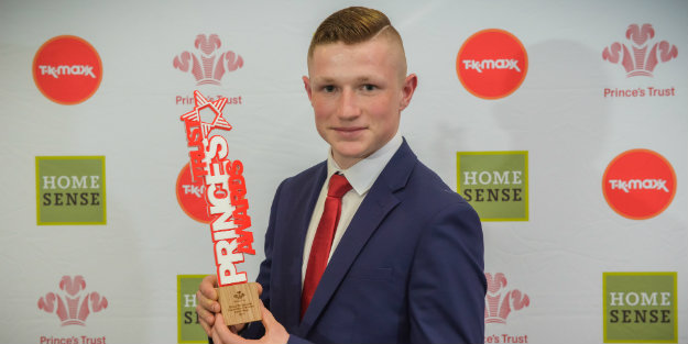 Young Person holding up a Prince's Trust Award