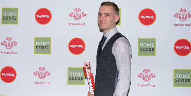 A young person holding Prince's Trust Award