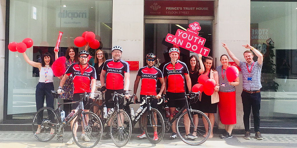 A group of Princes Trust staff and Oracle staff in front of The Princes Trust building. Oracle staff are by their bicycles.