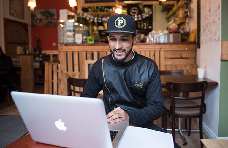 A young person sits by a table in a cafe using his laptop.