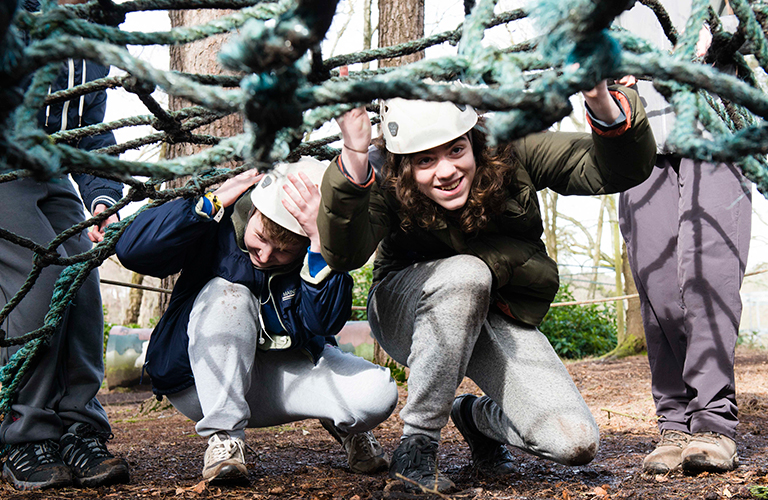 A group of young people are taking part in an obstacle course