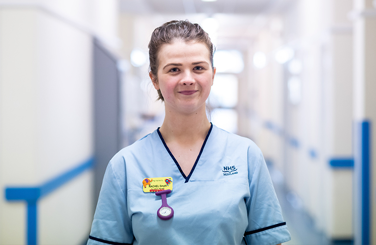 Female wearing nurse scrub standing hospital hallway