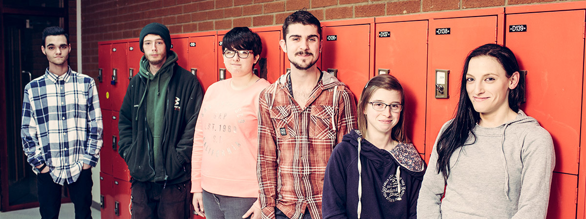 Group of six young people stand in front of a red locker