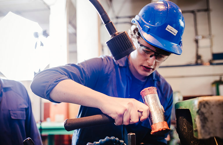 A young person is in a workshop wearing protective clothing and holding a hammering tool.