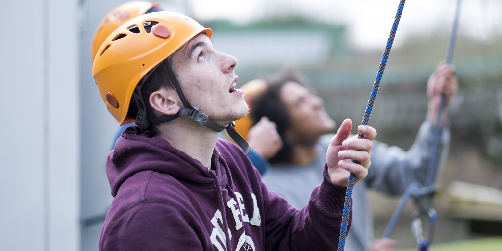 Young man at Team programme about to go on the climbing wall