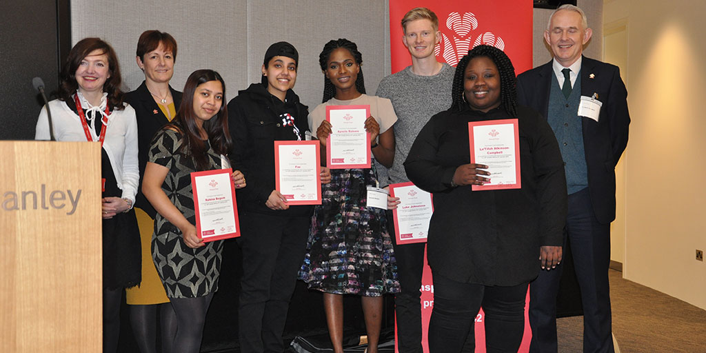 Young people holding up certificates