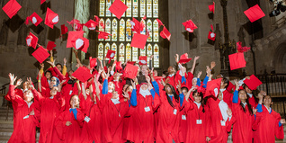 Primary school students in red gowns throw graduation hats into the air