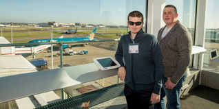 Celebrate Success London and South East regional award finalists Alex (left) and (Alan) right looking out over an aeroplane at Heathrow Airport