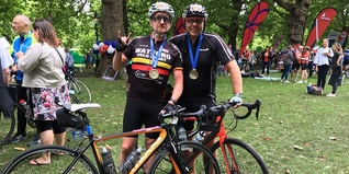 Mike and Matt standing by their bikes wearing a medal round their neck