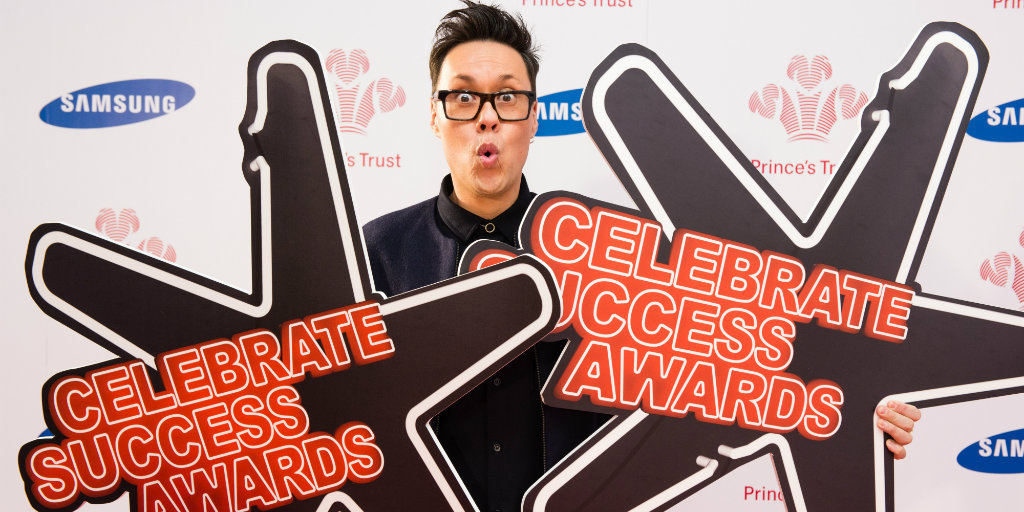 Gok Wan holding up two cut-out stars at Celebrate Success