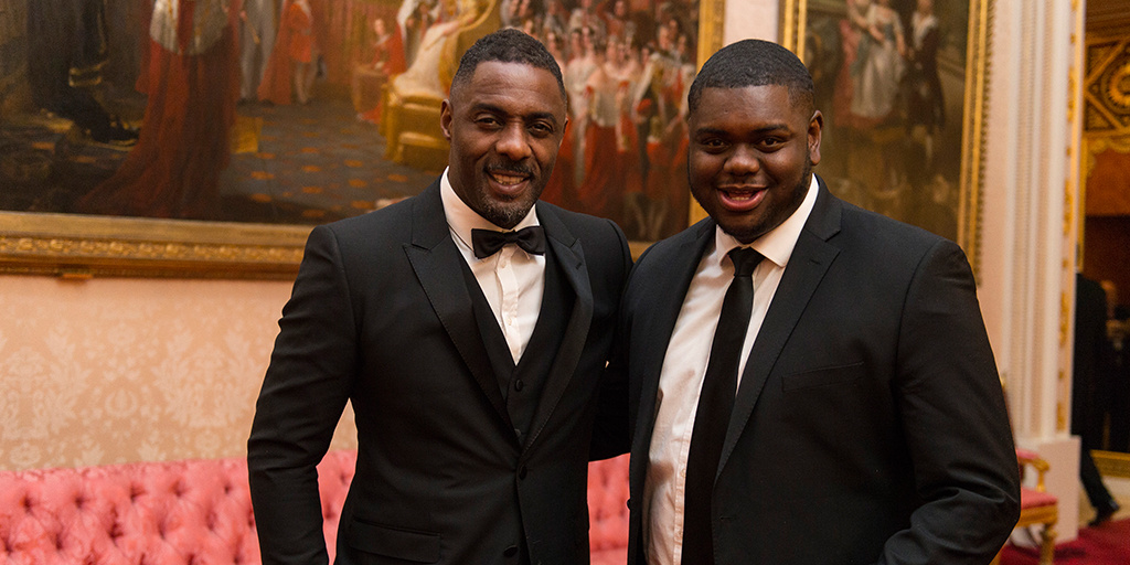 Idris Elba with young person at reception event