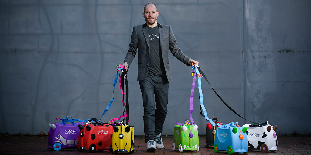 Rob Law, founder of Trunki, standing with seven Trunkis