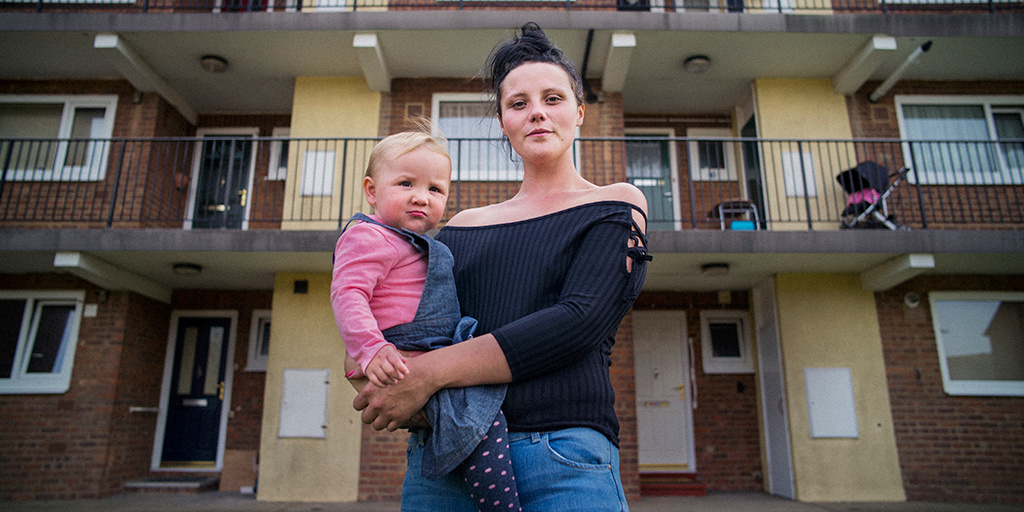 Mother holding toddler outside of housing estate