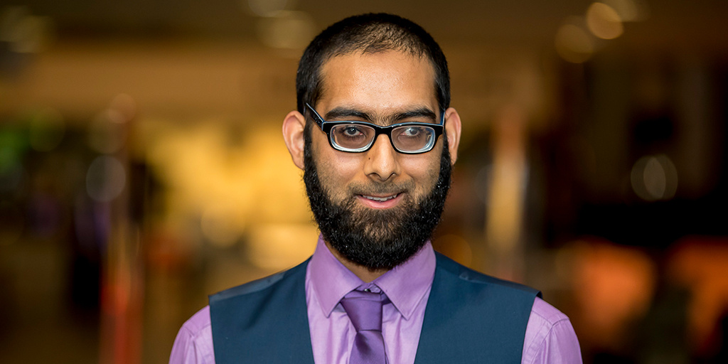 Aadam Hajat holding his Princes trust 'Young Ambassador' award wearing a purple shirt, purple tie and black glasses.