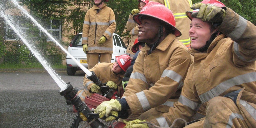 Fire and Rescue Service personnel teaching young people to use firehoses