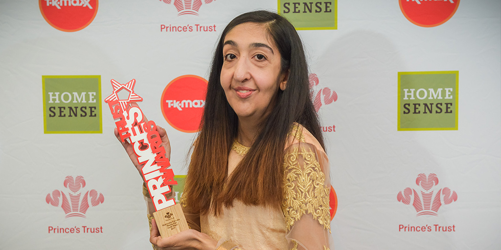 Hashmina Rahman holding her Princes Trust 'The Rising Star Award' wearing a gold dress.
