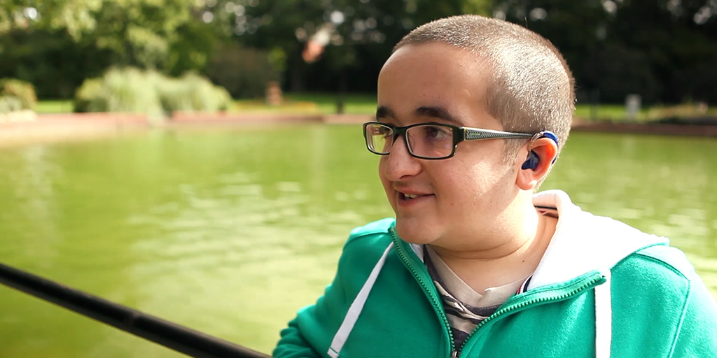 Thomas Nobrega in a talking gesture leaning on a rail. He is wearing an hearing aid, glasses and a green hoodie.