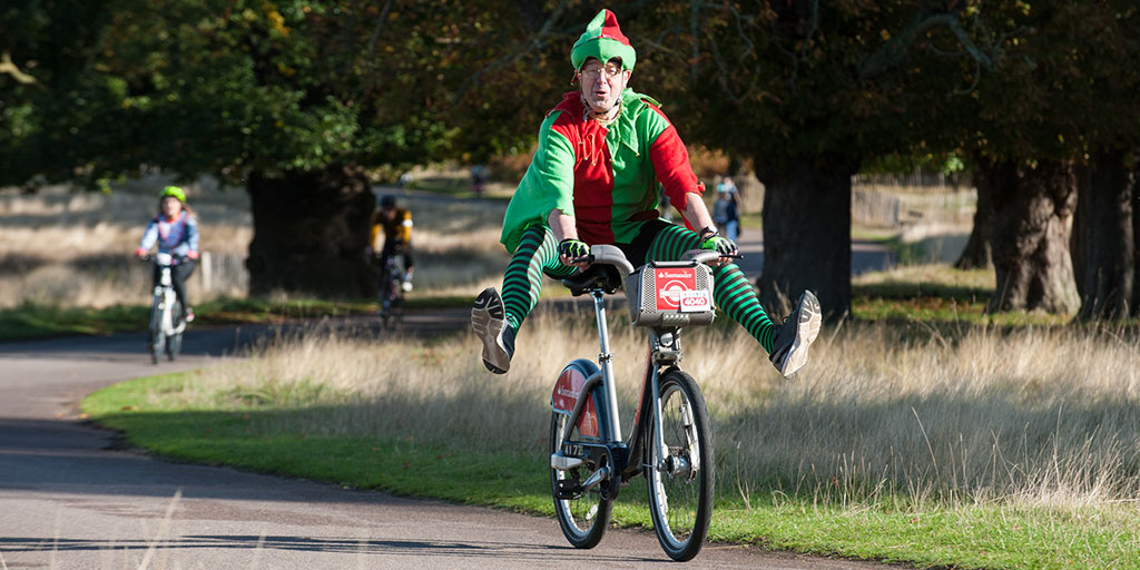 Man dressed in an elf suit cycling through Richmond Park